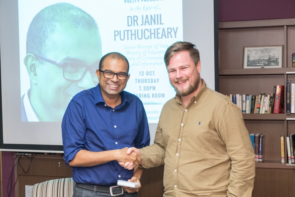 Dr Janil Puthucheary receives a token of appreciation from Mr Mike Grainger. a Fellow of Tembusu College
